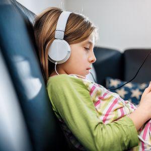 tyttö kuuntelee musiikkia kuulokkeilla