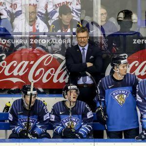 Suomen pelaajia vaihtoaitiossa, päävalmentaja Jukka Jalonen seisoo pelaajien takana.