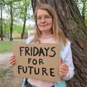 """Emma Pohja pitelee """"Fridays for Future""""-kylttiä"""