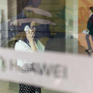 Nainen puhuu puhelimeen Huawein pääkonttorissa.