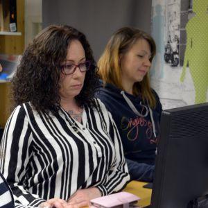 Kolme naista koululuokassa tietokoneiden ääressä,