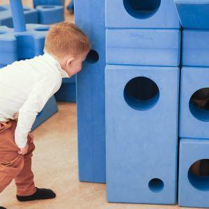 Lapsi katsoo liikkuvan leikkipuiston rakenteissa olevaan aukkoon.
