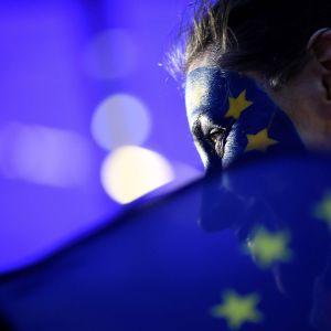 Nainen ja Euroopan lippu Euroopan parlamenttirakennuksen edessä vaali-iltana.