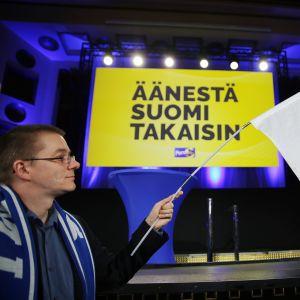 mies heiluttaa suomen lippua vaalivalvojaisissa