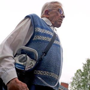 Lieksalainen Antero Leinonen ulkoilee lisähappisäiliön kanssa.