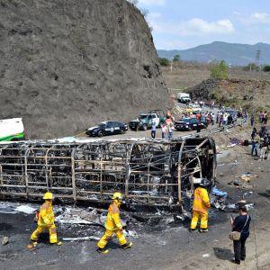 Pelastushenkilökunta jatkaa onnettomuuspaikan raivausta Meksikon Coatzacoalcosissa. Paikalla on myös poliisiautoja ja uteliaita siviilihenkilöitä.