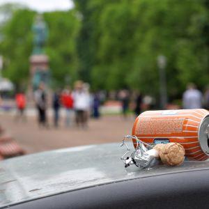 Tyhjä lonkerotölkki ja samppanjapullon korkki Esplanadin puistossa Helsingissä lauantai-iltana ensimmäinen kesäkuuta 2019.