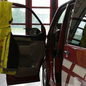 Päivystävän palomestarin takki roikkuu paloauton ovessa.