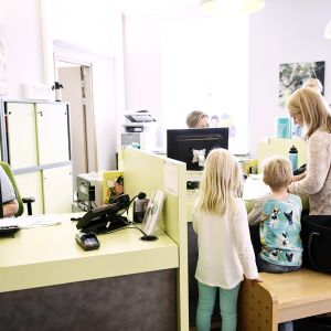 Äiti lapsineen lääkäriaseman vastaanottotiskillä Helsingissä