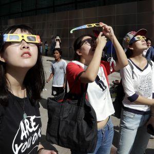 Kiinalaiopiskelijoita katsomassa taivaalle suojalasit silmillään.