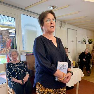 Nainen seisoo vanhustentalossa asukkaiden keskellä.