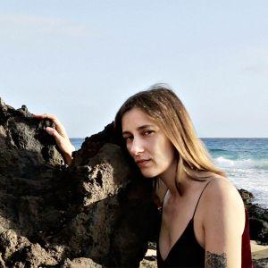 Nainen on meren äärellä ja nojaa kalliolohkareisiin.