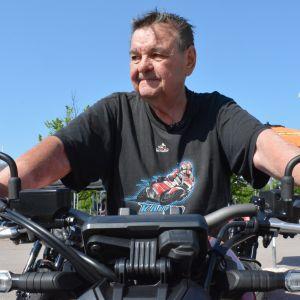 Mies istuu moottoripyörän päällä
