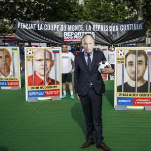 Venäjän lehdistönvapauden tila on usein huolenaiheena. Tässä Vladimir Putin -naamioon pukeutunut mies seisoo Venäjällä vangittujen toimittajien kuvien edessä mielenosoituksessa Pariisissa kesäkuussa 2018, jalkapallon MM-kisojen avajaisten alla.