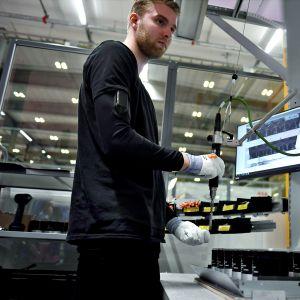 Tuotantotyöntekijä Leevi Pienihäkkinen tekee kondensaattorin osakokoonpanoa teollisen tekoälysovelluksen avustamana ABB:n tiedotustilaisuudessa 5. kesäkuuta 2019.