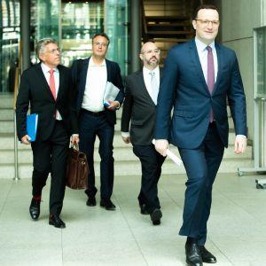Terveysministeri Jens Spahn sekä asiantuntijat Martin Burg, Peer Briken ja Jörg Litwinschuh-Barthel kävelevät käytävällä.