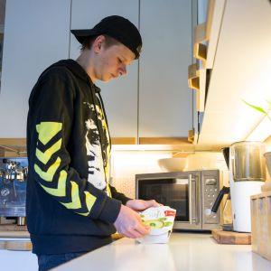 Nuori mies Miro, lämmittää mikroruokaa keittiössä