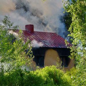 Omakotitalon palosta nousee sankkaa savua.