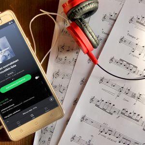 Nuottipapereita ja puhelin, jossa auki Spotify