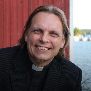 Kirkkoherra Kimmo Reinikainen seisoo mökin edessä.