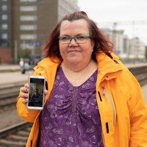 Jaana Nordlund näyttää puhelimelta kuvaa miehestään Aimosta Tampereen rautatieasemalla
