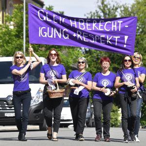 Kuusi naista marssii mielenosoitusjulistetta kantaen.