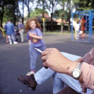 Isä tupakoi lasten leikkikentällä.