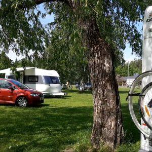 Leirintäalueen kentällä auto, asuntoauto ja asuntovaunu.