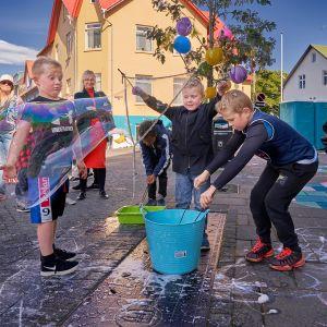 Islantilaiset lapset tekevät saippuakuplia.