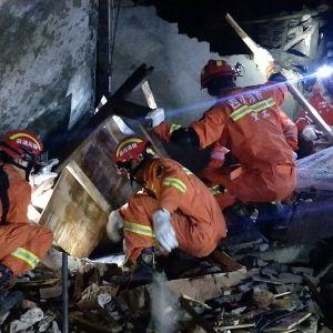Pelastajat etsivät maanjäristyksen uhreja romahtaneen rakennuksen raunioista.