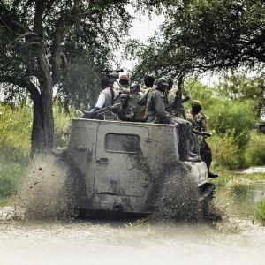 sotilaita miehistönkuljetusvaunun päällä ajamassa vesilätäkön läpi
