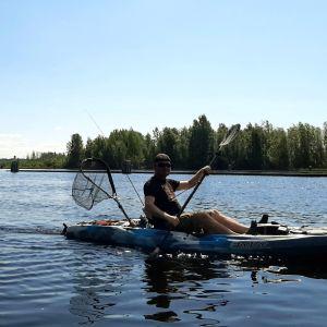 Matti Pesonen kanootissa, haavi ja virveli.
