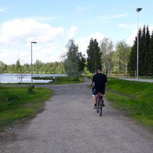 Polkupyöräilijä ajaa soraisella tiellä.