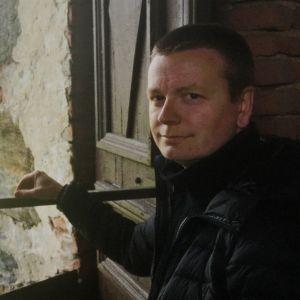Suntio Mikko Kohonen Kangasalan kirkon tornissa avoimen ikkunaluukun ääressä
