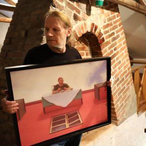 Kaj Stenvall pitää Putin-aiheista maalausta käsissään.