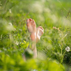 Paljaat jalat kukkakedolla.