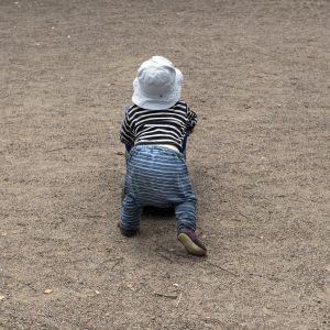Pieni lapsi leikkii leikkipuistossa.