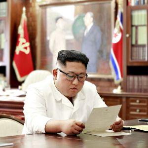 Pohjois-Korean valtiollisen uutistoimiston (KCNA) välittämä kuva Kim Jong-unista lukemassa Donald Trumpin kirjettä.