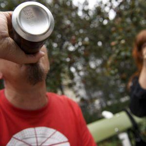 Mies ja nainen juomassa alkoholijuomia puistossa.