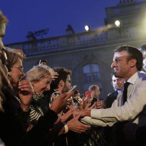 Emmanuel Macron kättelee ihmisiä.