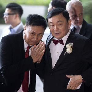 Kuvassa Thaksin Shinawatra oikealla ja vasemmalla toinen mies, jonka kädet ovat wai-tervehdyksen asennossa.