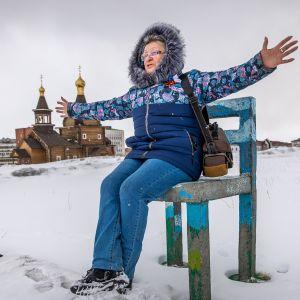 Venäläisrouva Larisa istuu talvimaisemassa kädet levällään.