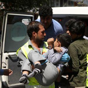 Ensiapuhenkilö kantaa haavoittunutta oppilasta ampulanssiin Kabulissa 1. heinäkuuta.