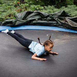 Lapsi hyppii trampoliinilla mahallaan
