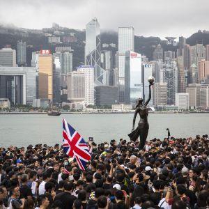Valtava ihmisjoukko. Keskellä patsas. Taustalla Hongkongin pilvenpiirtäjiä.