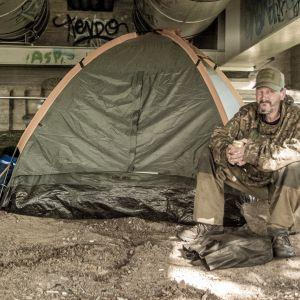 Markku Korhonen istuu teltan vieressä