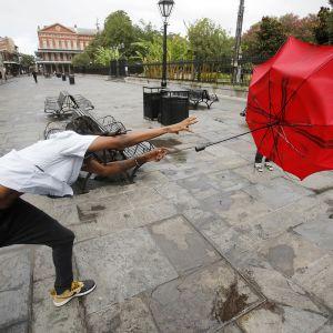 Sateenvarjo lentää miehen kädestä New Orleansissa.
