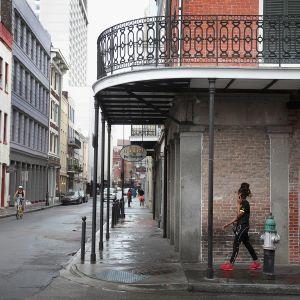 Nainen kävelee autiolla kadulla New Orleansissa.
