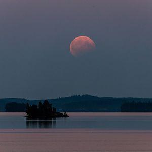 Osittain pimentynyt punertava kuu järven yllä.