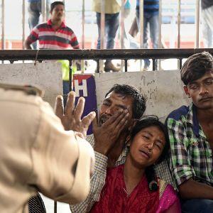 Rautatieaseman turvamies tarkkailee pidätettyjä Bangladeshiläisiä.